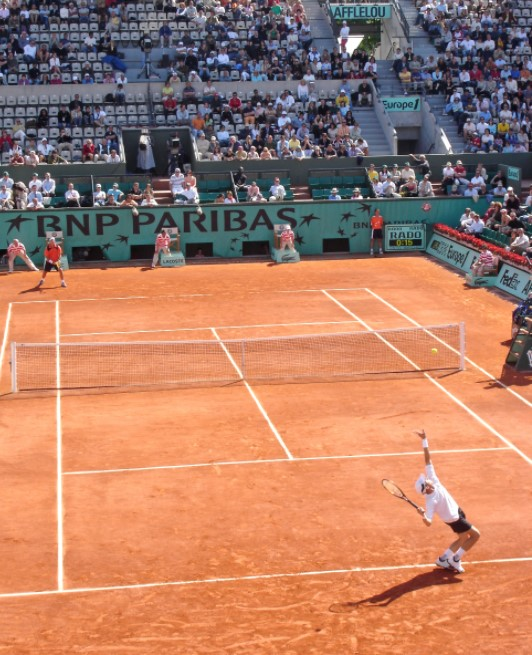 Which grand slam tennis tournament is played on red clay courts